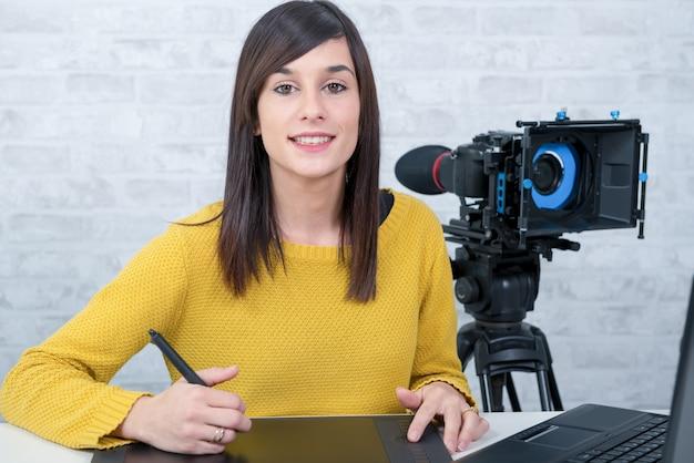 Progettista di giovane donna che utilizza la tavoletta grafica per l'editing video