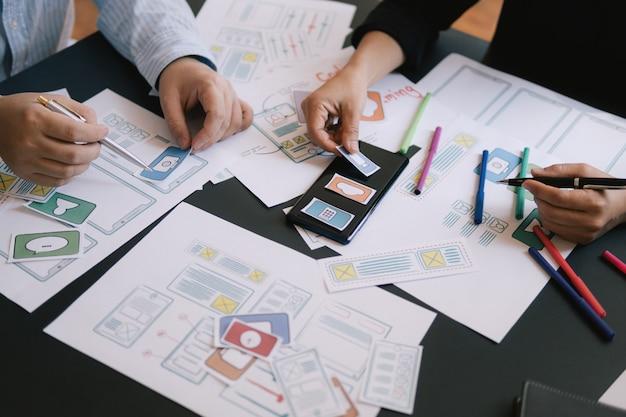 Progettista di ui ux del primo piano che incontra il prototipo dell'applicazione di disposizione dello smartphone di web