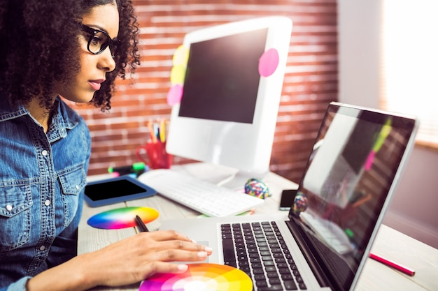 Progettista femminile casuale che per mezzo del computer portatile