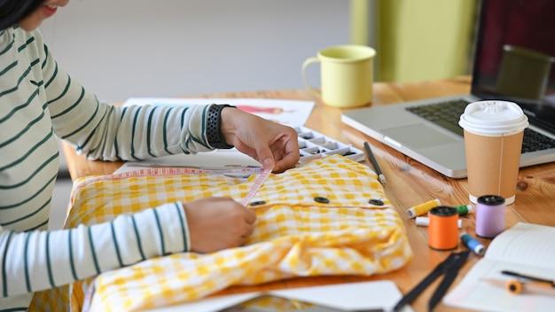 Progettista femminile del colpo ritagliato che lavora il suo progetto.