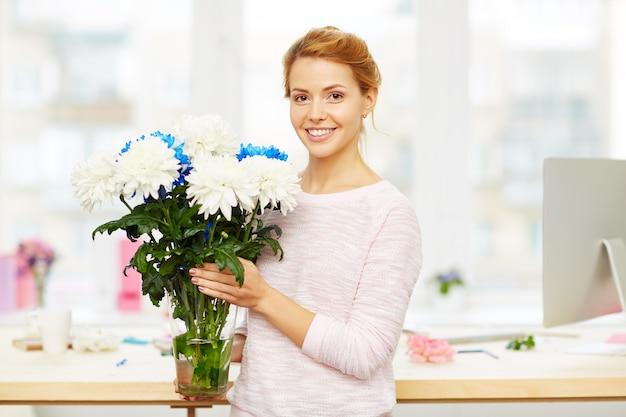 Progettista floreale sorridente sul lavoro