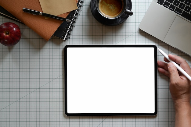 Progettista grafico che lavora con tavoletta digitale nel posto di lavoro di studio