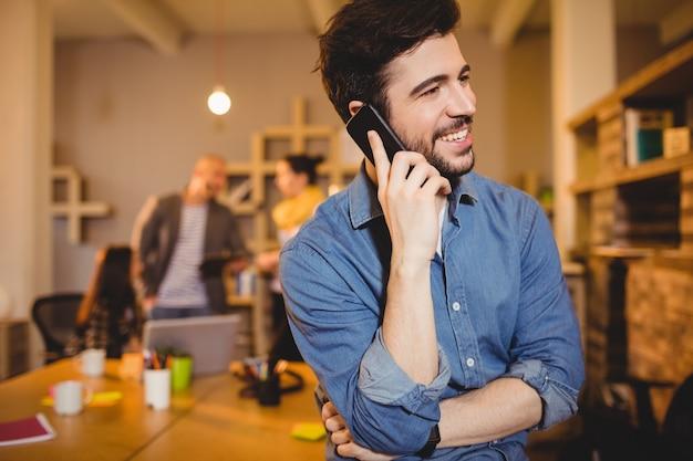 Progettista grafico che parla sul telefono cellulare