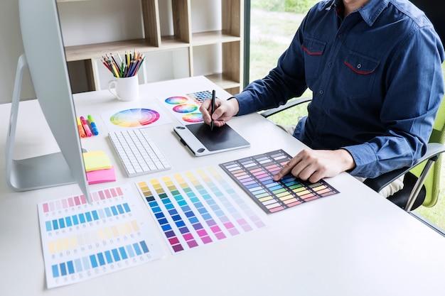 Progettista grafico creativo che lavora alla selezione dei colori e al disegno sulla tavoletta grafica sul posto di lavoro