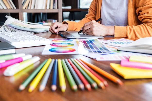 Progettista grafico creativo che lavora alla selezione dei colori e al disegno sulla tavoletta grafica