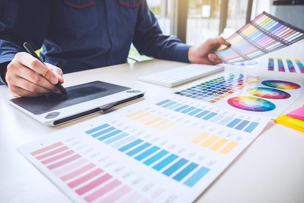 Progettista grafico creativo che lavora sulla selezione dei colori e sui campioni di colore
