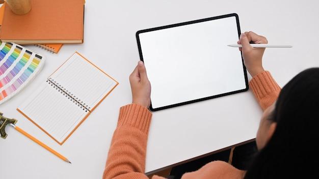 Progettista grafico di vista superiore che lavora al computer portatile del modello con lo schermo vuoto.