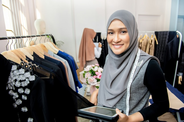 Progettista musulmano asiatico della donna nel suo negozio del sarto