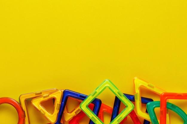 Progettista o costruttore magnetico per bambini. dettagli, forme geometriche su sfondo giallo. disteso, copia spazio.
