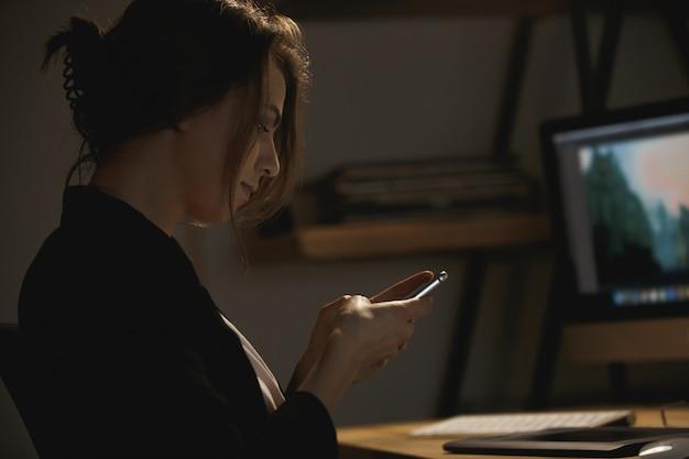 Progettista serio della giovane signora che si siede all'interno di chiacchierare di notte