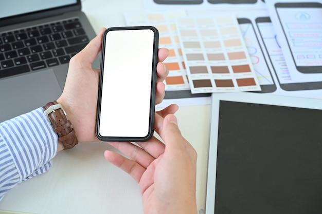 Progettista ui ui che tiene il telefono cellulare con schermo vuoto