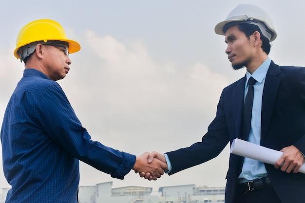 Progetto di costruzione della costruzione di successo della costruzione dell'ingegnere delle mani dell'uomo d'affari shake, accordo di scossa della mano