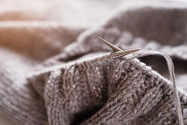 Progetto di maglia incompleta con il primo piano di aghi di metallo. lavorare a maglia un maglione di lana grigio. il concetto di hobby, creatività, ricamo, fatto a mano.