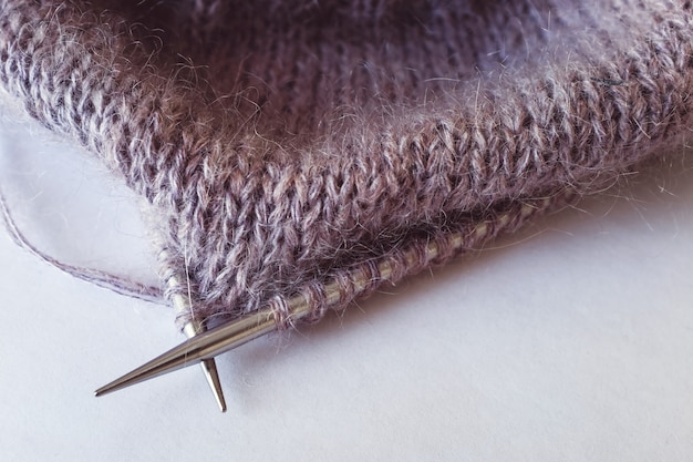 Progetto di maglia incompleta con il primo piano di aghi di metallo