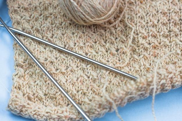 Progetto di maglieria in corso. un pezzo di maglia con un gomitolo di lana e maglieria. prodotti per cucito, maglieria.