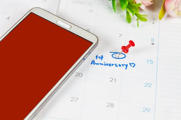 Programma di celebrazione di anniversario di parola sul calendario con microtelefono rosso.