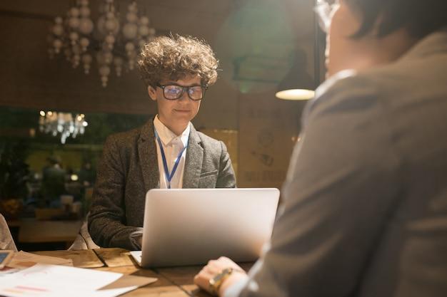 Programmatore astuto che utilizza computer portatile nell'ufficio scuro