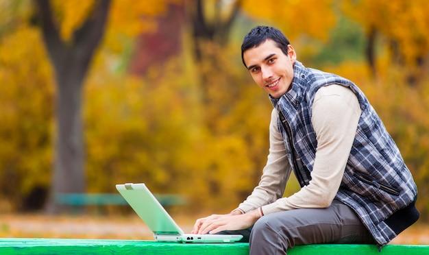 Programmatore con il taccuino che si siede nel parco di autunno