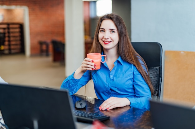Programmatore della giovane donna che si siede in un companyfice nel computer anteriore con una tazza rosa. ingegnere informatico professionista che esamina macchina fotografica e sorridere. lavoro software