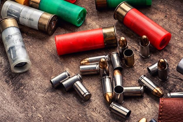 Proiettili di pistola pistola e rivista sparso sul tavolo di legno