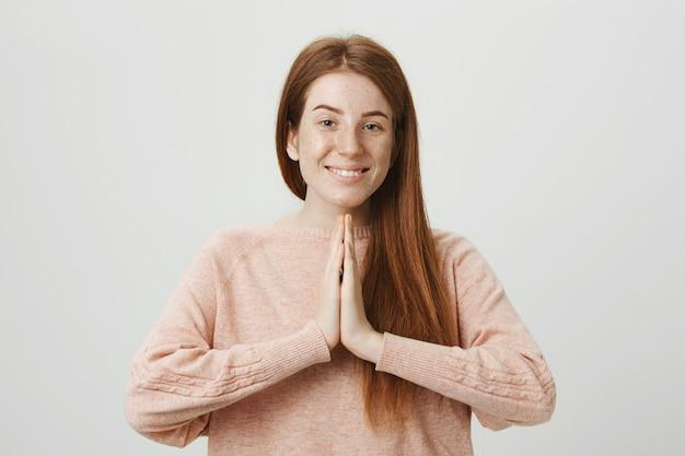 Promettente ragazza dai capelli rossi che supplica ogd, pregando o implorando favore