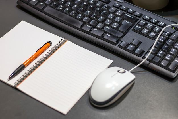 Pronto per il lavoro. chiuda sulla vista da sopra della penna e della tastiera del blocco note