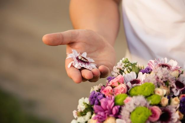 Proposta di matrimonio. anello di fidanzamento sul fiore colorato a portata di mano dell'uomo. il ragazzo presenta una proposta con anello nuziale dorato