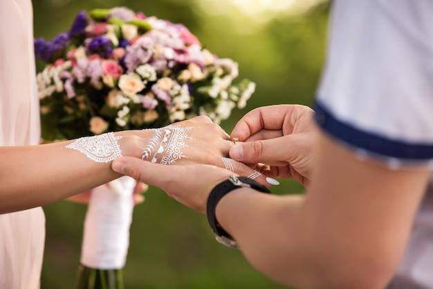 Proposta di matrimonio o fidanzamento di coppia indiana. anello di fidanzamento a disposizione della ragazza con l'ornamento di mehendi alla cerimonia di nozze