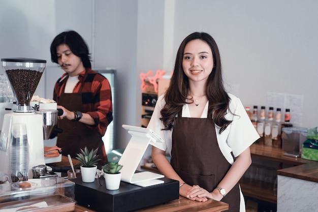 Proprietario asiatico del caffè che sorride alla macchina fotografica