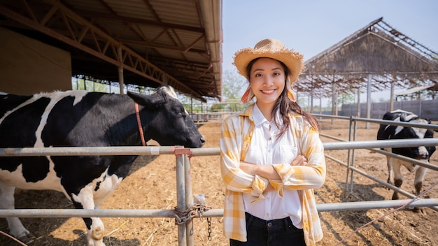 Proprietario asiatico del ritratto di un allevamento di mucche in piedi nella fattoria