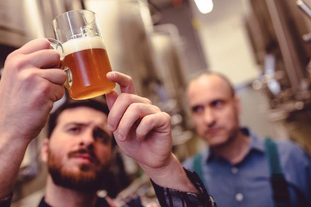 Proprietario che controlla birra in tazza