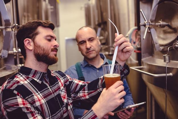 Proprietario che esamina birra in vetro
