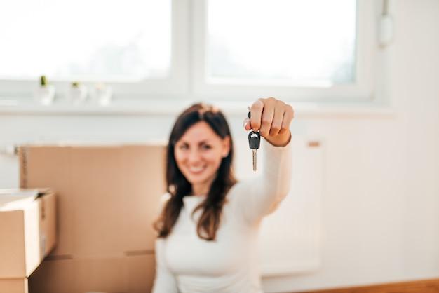 Proprietario di appartamento femminile felice che mostra le chiavi di nuova casa. focus di un primo piano.