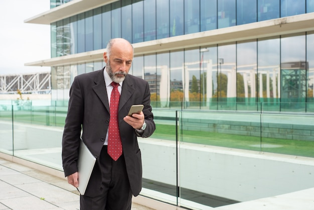 Proprietario di società dai capelli grigio messo a fuoco che per mezzo dello smartphone