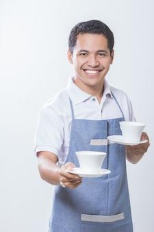 Proprietario di un piccolo negozio di caffè con due tazze di caffè