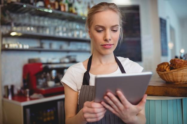 Proprietario femminile che per mezzo della compressa al caffè
