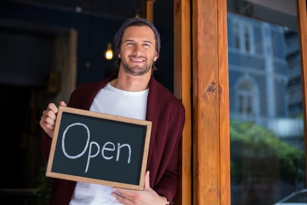 Proprietario sorridente che si appoggia con il cartello aperto in caffè