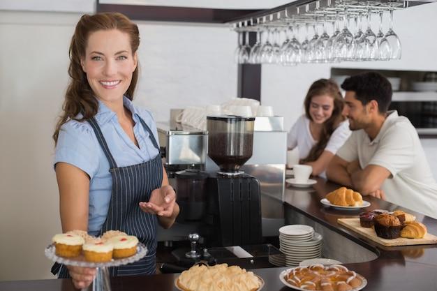 Proprietario sorridente del caffè che tiene gli spuntini dolci con le coppie al contatore in caffetteria