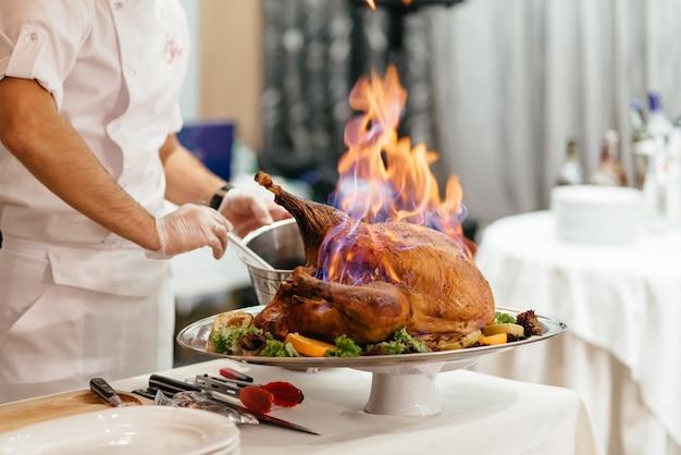 Prosciutto affettato arrostito di natale sul piatto con la forcella, coltello e decorazione festiva su fondo rustico scuro