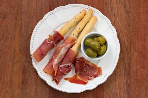 Prosciutto con olive sul piatto bianco su sfondo marrone