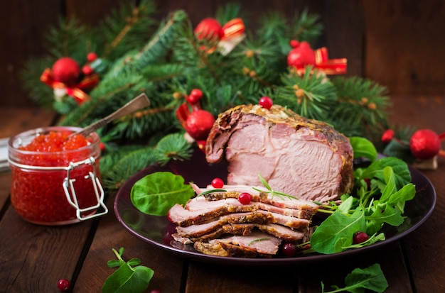 Prosciutto cotto di natale e caviale rosso, servito sul vecchio tavolo di legno.