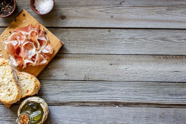 Prosciutto e pane su legno