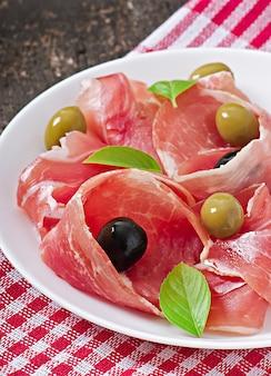 Prosciutto, olive, basilico su legno vecchio