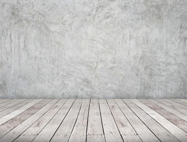 Prospettiva della stanza, muro di cemento grigio del grunge e terra della plancia di legno
