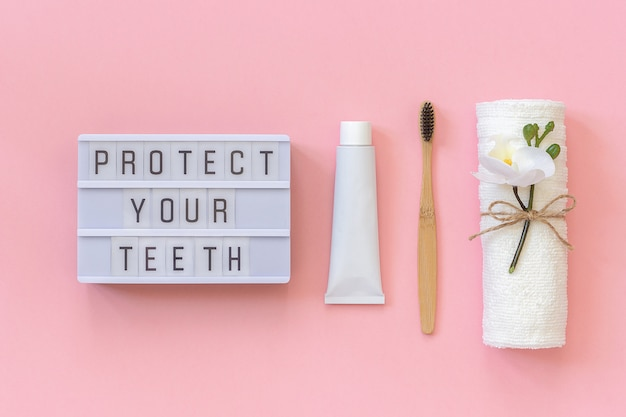 Proteggi il testo dei denti su una scatola luminosa e un pennello in bambù naturale ecologico per denti, asciugamano, tubetto di dentifricio.