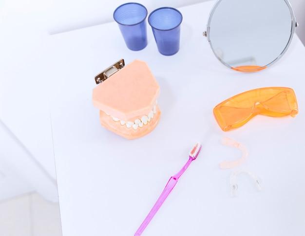 Protesi dentaria; occhiali di sicurezza; spazzolino da denti; allineatore di specchi e denti sul tavolo