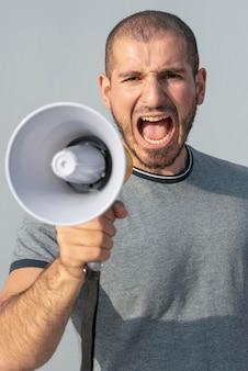 Protestatore di vista frontale con megafono che grida