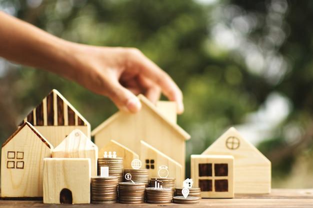 Protezione femminile delle mani il piccolo modello della casa di legno sul fondo del bokeh dell'albero e della plancia.