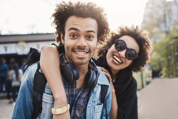 Protrait all'aperto di coppia afro-americana che abbraccia e sorride ampiamente alla macchina fotografica mentre si cammina nel parco ed esprime emozioni positive.