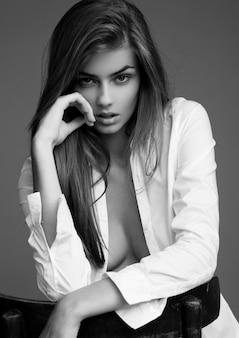Prova di modello con la giovane bella modella indossa camicia bianca seduto sulla sedia
